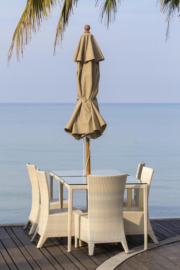 Белые стулья таблицы и ротанга в пустом кафе рядом с морской водой на пляже, Таиланде стоковые изображения