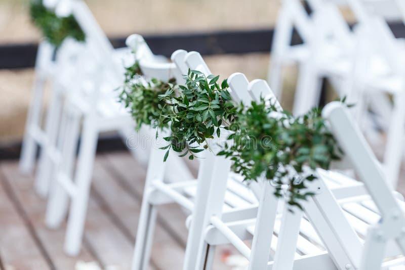 Белые стулья украшенные с растительностью и евкалиптом в z стоковое изображение