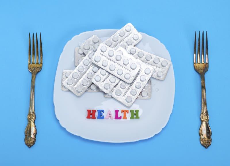 Белые таблетки в пакете на квадратной керамической плите стоковое изображение rf