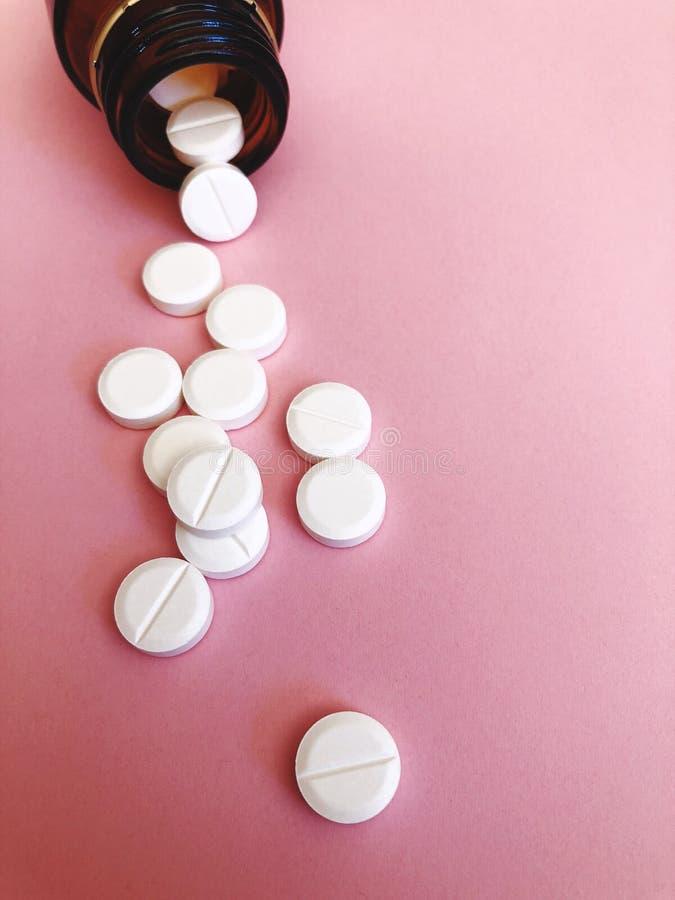 Белые таблетки на розовой предпосылке стоковые изображения