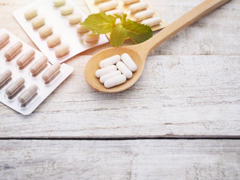 Белые травяные пилюльки в деревянном пакете ложки и волдыря стоковые изображения rf