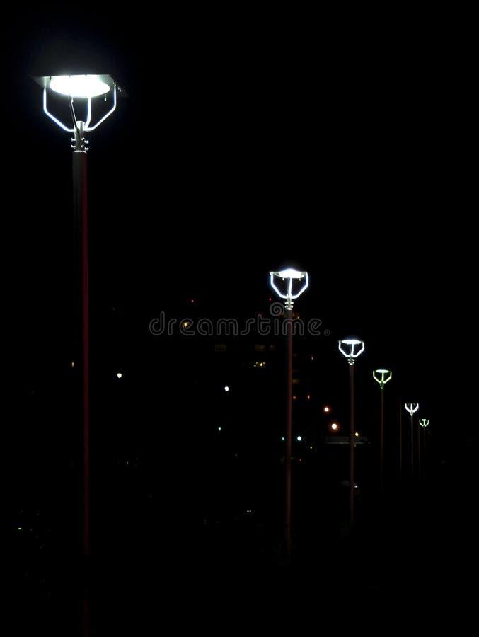 Белые уличные светы выровнялись вверх с красным поляком металла стоковое изображение