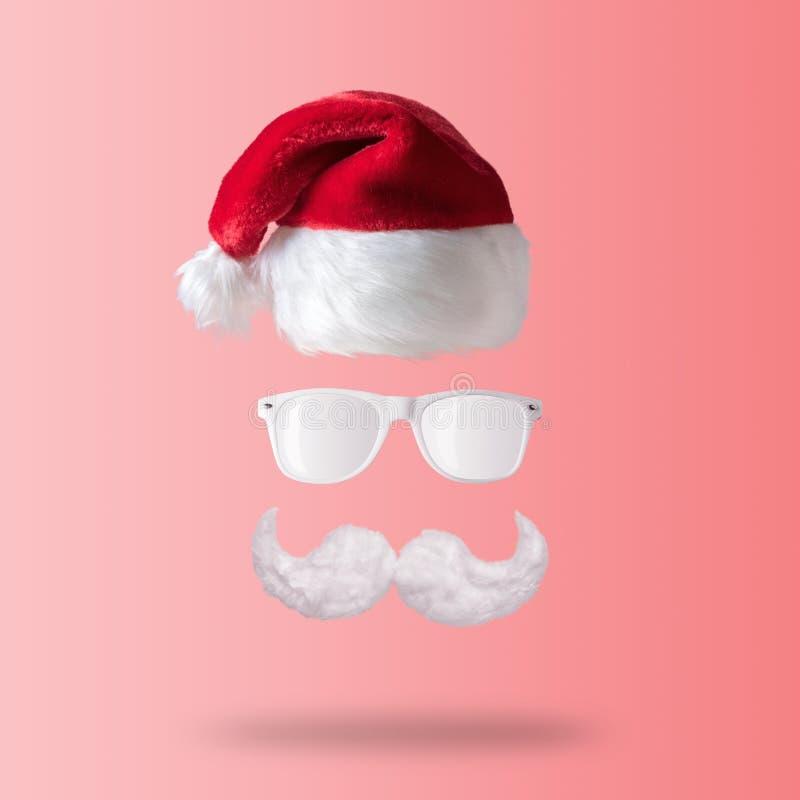 Белые усик, солнечные очки и шляпа хипстера Санта Клауса на розовой предпосылке Концепция Нового Года или рождества минимальная стоковые изображения rf