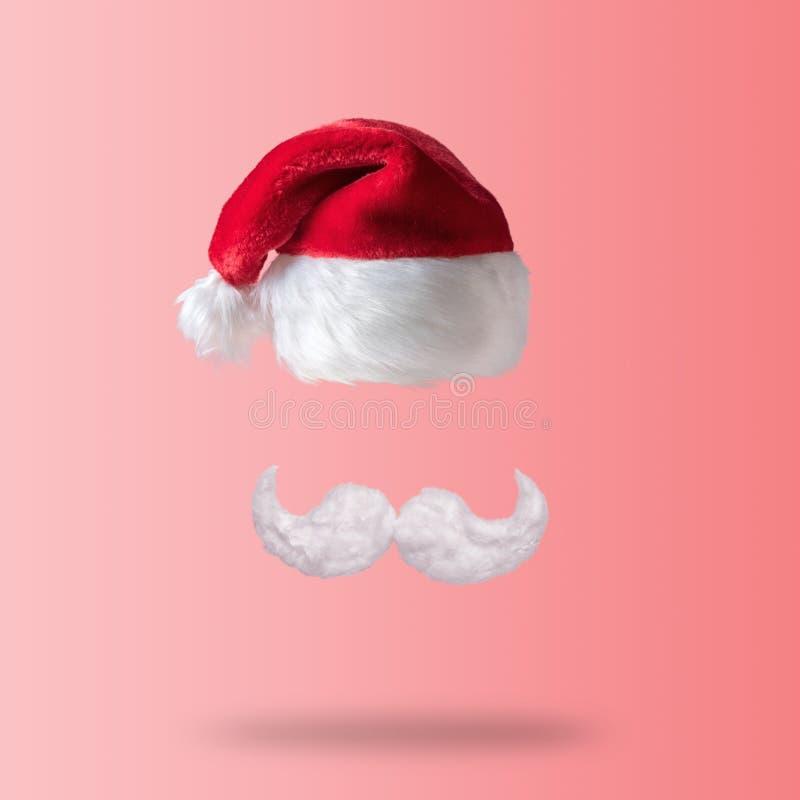 Белые усик хипстера и шляпа Санта Клауса на розовой предпосылке Концепция Нового Года или рождества минимальная стоковая фотография
