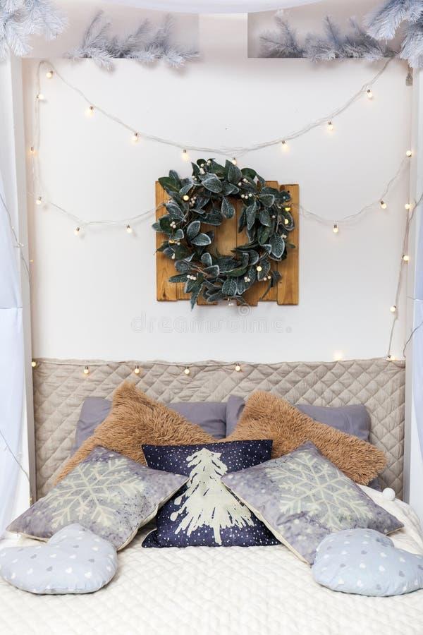 Белые уютные кровать и света рождества стоковая фотография rf