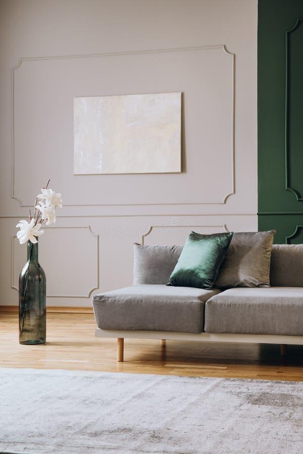 Белые цветки в большой зеленой форме бутылки как ваза рядом с серым settee в модном интерьере живущей комнаты стоковые фотографии rf