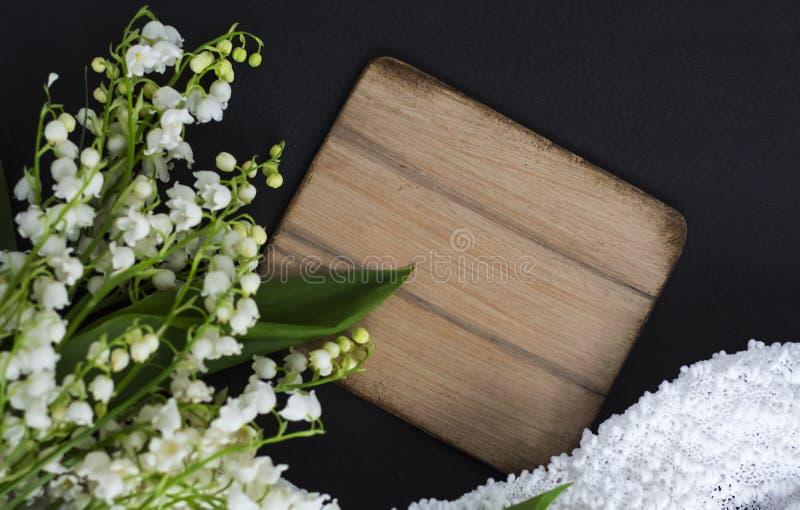 Белые цветки ландыша на черной предпосылке с деревянной доской для копирования космоса и чувствительной ткани стоковые фотографии rf