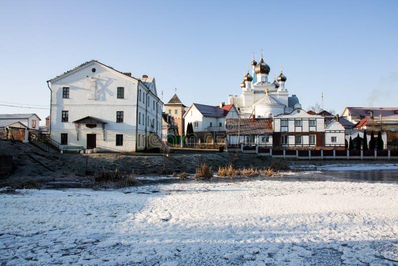 Белые церковь и дома на банках реки, ландшафта зимы стоковое фото rf