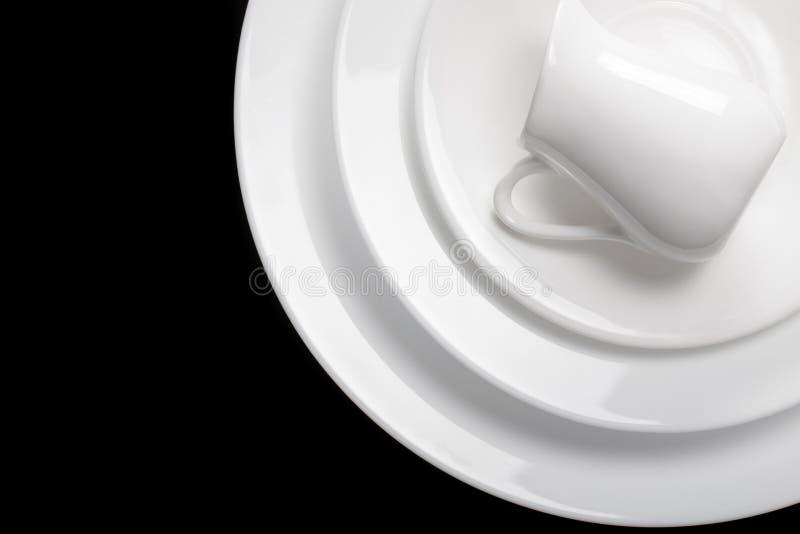 Белые чистые блюда сложены в стоге на черной предпосылке Красивейшая абстрактная предпосылка стоковое фото