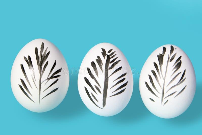 Белые яичка курицы украшенные для пасхи на голубой предпосылке Черное перо нарисовано на яичке стоковое изображение
