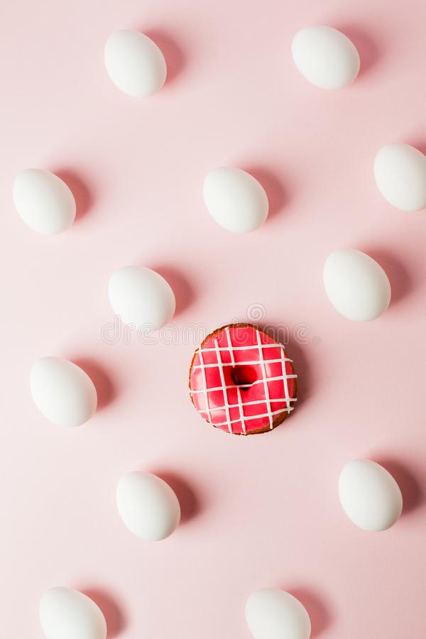 Белые яйца и розовый донут на светлом - розовая предпосылка с отражением теней и космоса экземпляра план к пасхе Плоское положени стоковая фотография
