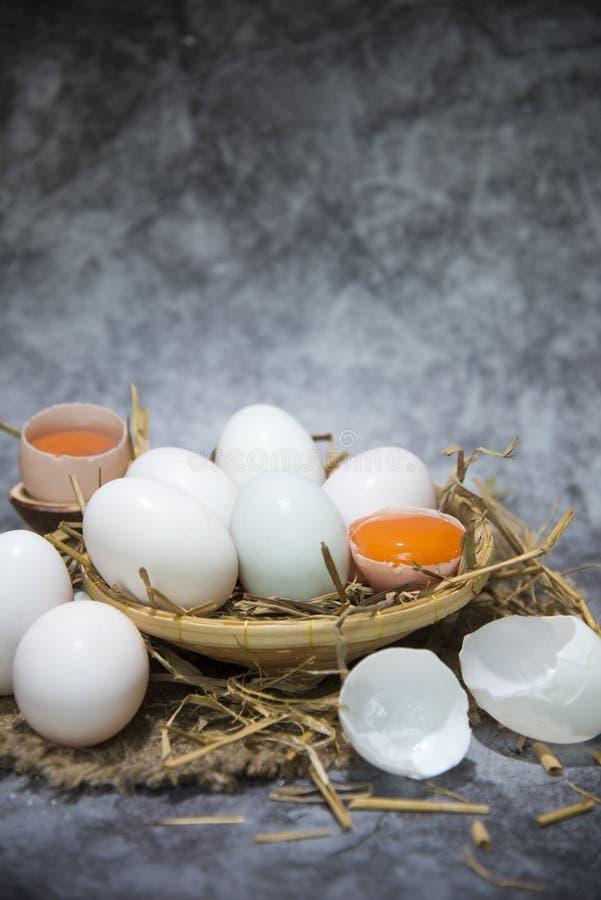 Белые яйца от корзины в соломе, сломленном яйце над белизной стоковые фото