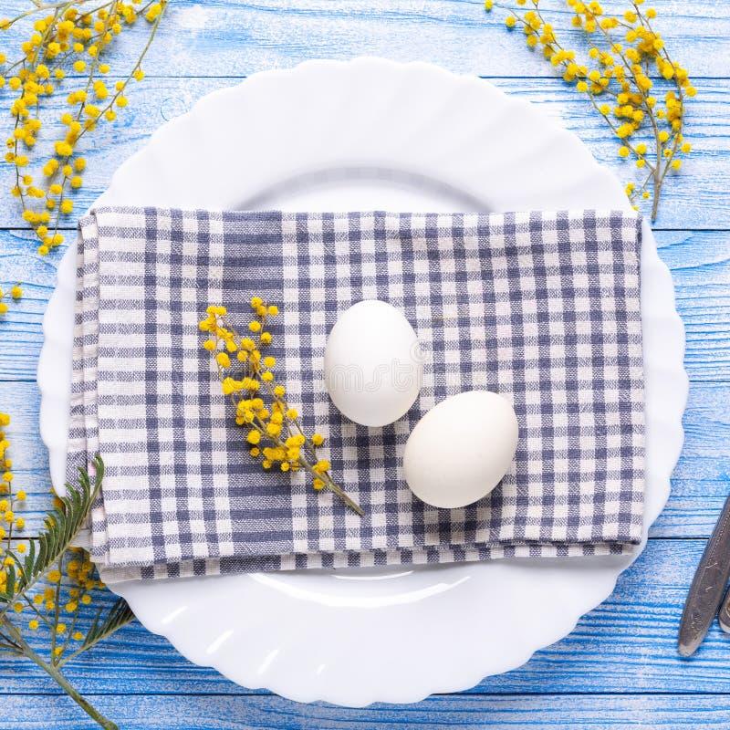 Сервировка стола пасхи Белые яйца, салфетка на плите, цветки мимозы, вилка, нож на голубом квадрате деревянного стола стоковые фото