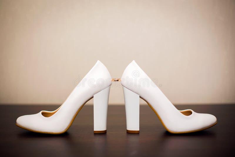 Белые bridal ботинки и обручальные кольца стоковые фото