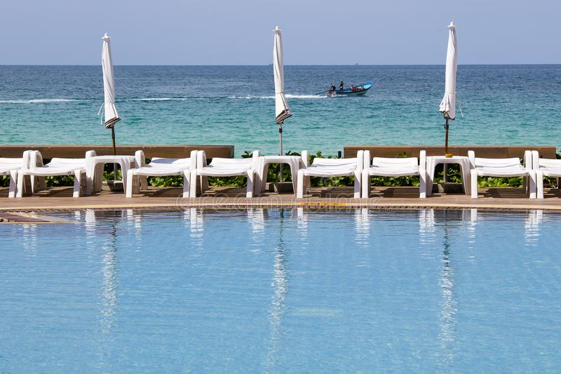 Белые sunbeds и зонтики на пляже около бассейна и моря Koh Phangan острова, Таиланд стоковое фото rf