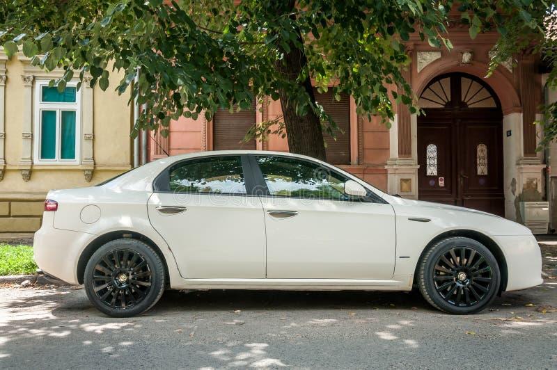 Белый автомобиль Romeo 159 альфы с черными колесами сплава припарковал на улице стоковое фото