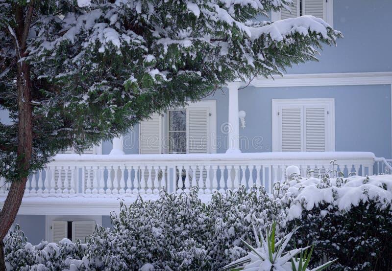 Белый балкон голубого дома за снежными заводами стоковое изображение rf
