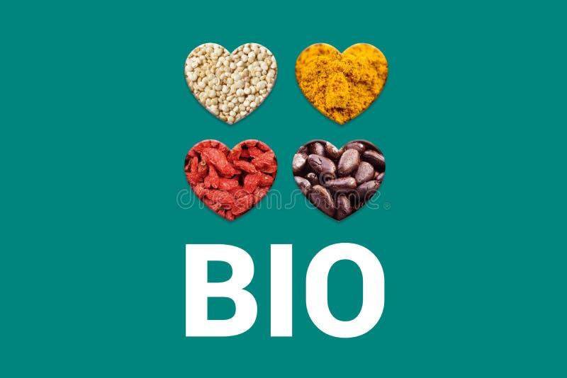 Белый био текст на предпосылке и сердцах бирюзы с nibs какао, белые зерна квиноа, высушенные ягоды goji и стоковые фотографии rf