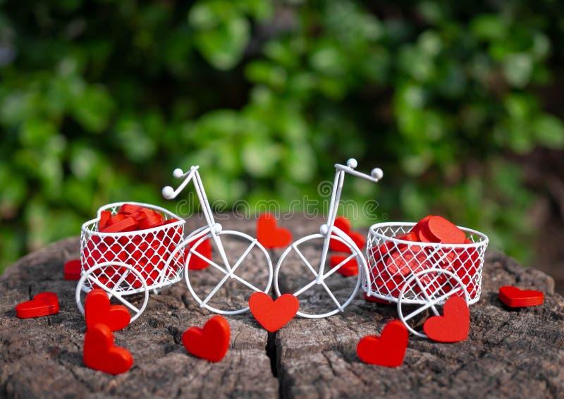 Белый велосипед игрушки нося красные деревянные сердца Красные деревянные сердца падают на деревянный пол в форме Сердц игрушки т стоковая фотография rf