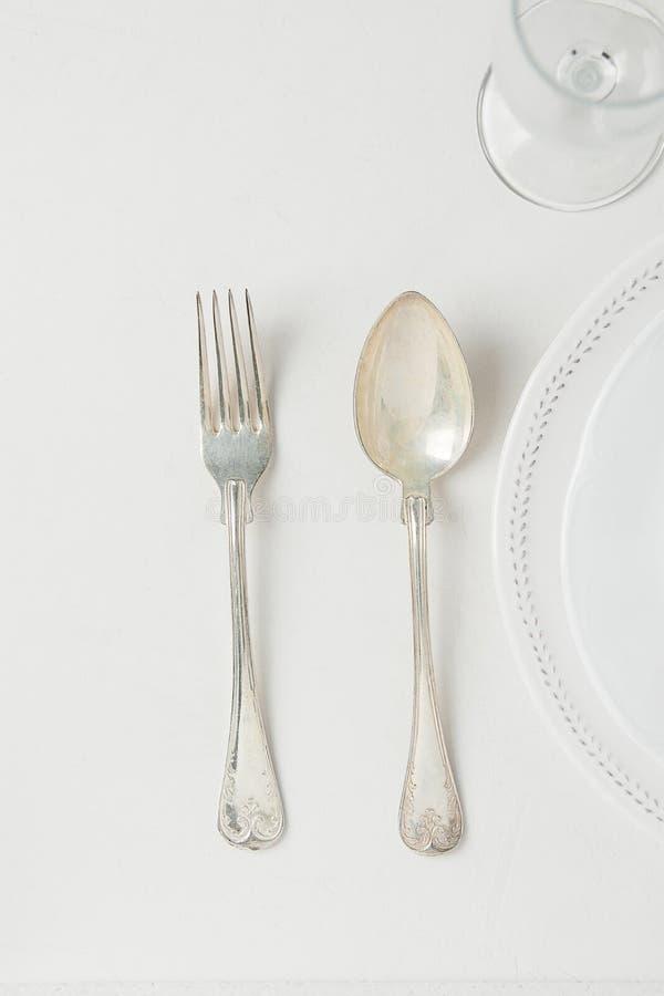 Белый винтажный пустой бокал ложки вилки серебра полкруга плит на конкретной столешнице Минималистская сервировка стола японского стоковые фото