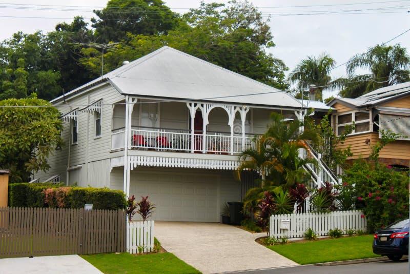 Белый дом queenslander с тропическими растительностью и высокими деревьями на день overcast в Австралии стоковые фотографии rf