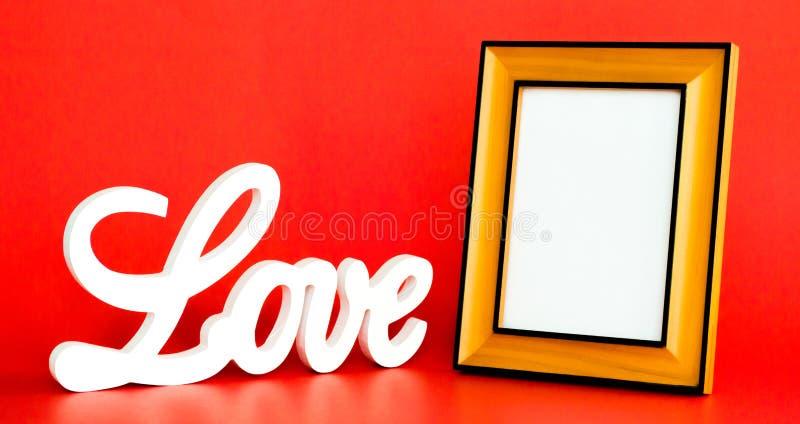 Белый знак ВЛЮБЛЕННОСТИ и пустая картинная рамка на красной предпосылке стоковое изображение