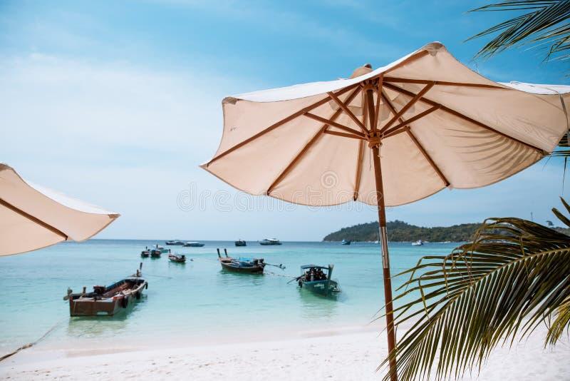 Белый зонтик на тропическом пляже на дневном времени со шлюпкой такси длинного хвоста стоковые фото