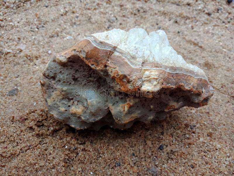 Белый и серый кристаллический камень с текстурой на песке текстурированные обои предпосылки, пляж океан стоковое изображение