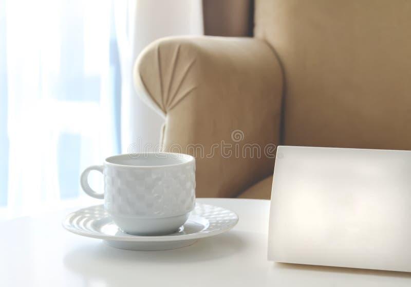 Белый картон знака с космосом экземпляра рядом с чашкой чая на белой таблице стоковое фото rf