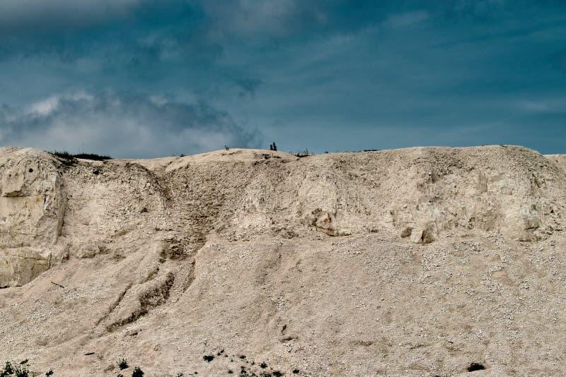 Белый карьер известняка на предпосылке голубого неба с облаками стоковые фотографии rf