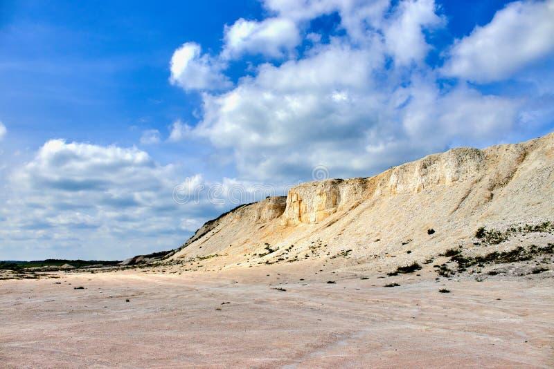 Белый карьер известняка на предпосылке голубого неба с облаками стоковое фото