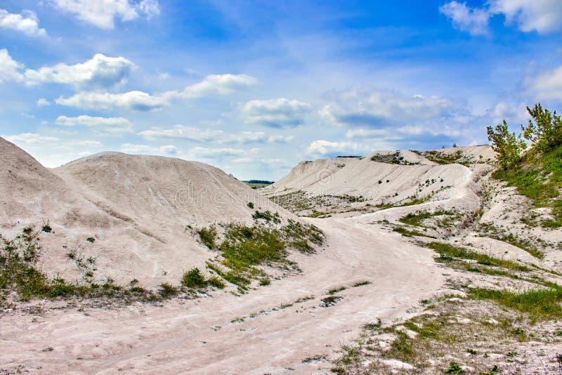 Белый карьер известняка на предпосылке голубого неба с облаками стоковые изображения
