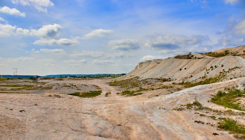 Белый карьер известняка на предпосылке голубого неба с облаками стоковые фото