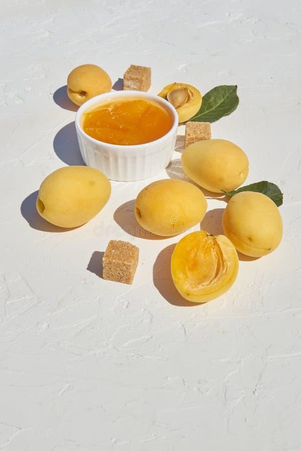 Белый керамический шар с домодельным органическим вареньем абрикоса и зрелыми абрикосами и желтым сахарным песком на белой предпо стоковое изображение