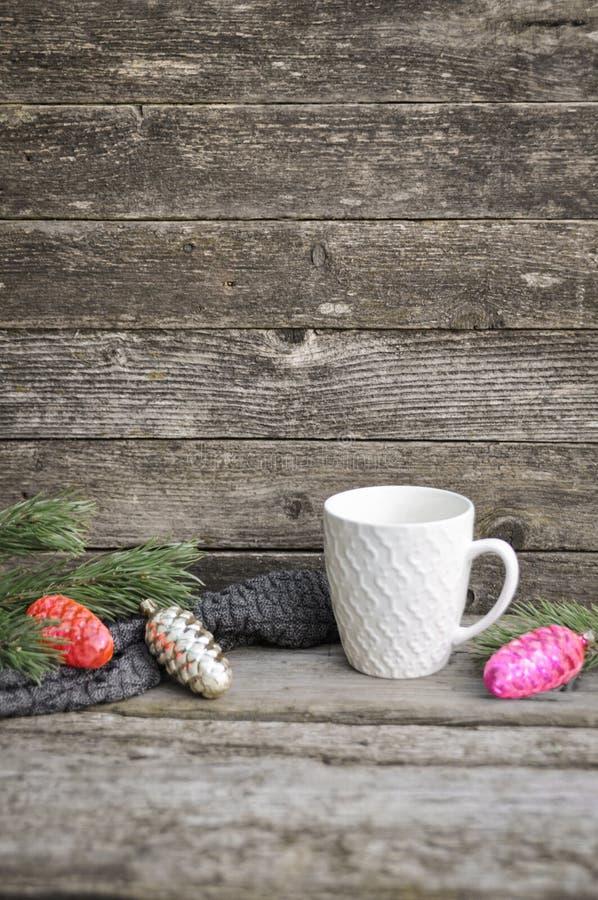 Белый круг с конусами картиной, украшением рождественской елки и зеленой сосной разветвляет на связанном свитере Деревянная серая стоковое изображение