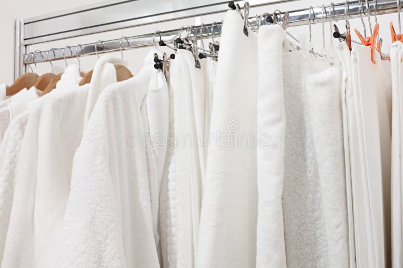 Белый купальный халат с вешалкой и полотенцем в шкафе на гостиничном номере Закройте вверх вешалки одежд и купального халата в шк стоковая фотография