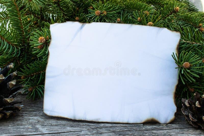 Белый лист бумаги, который сгорели вдоль краев и зеленых ветвей рождественской елки на предпосылке старых, деревянных доск стоковое фото