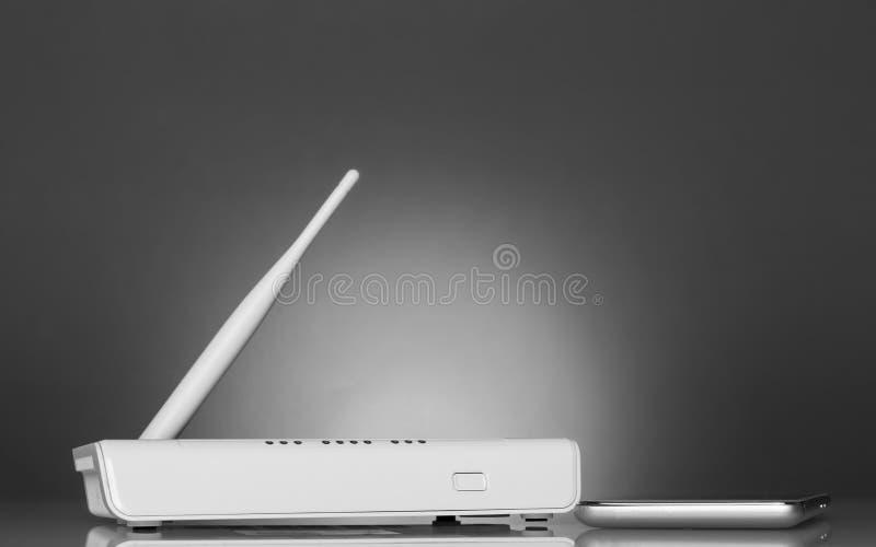 Белый маршрутизатор и смартфон на яркой красивой серой предпосылке стоковые изображения