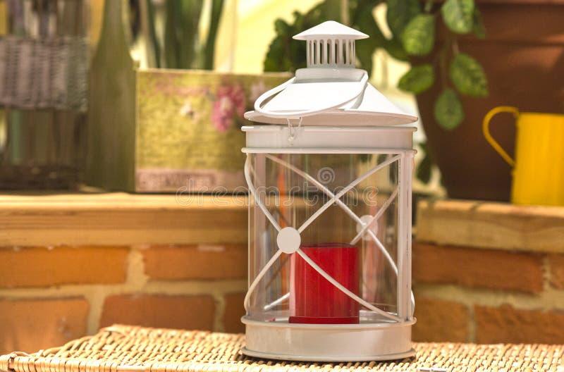 Белый металл с подсвечником стеклянной стены с красной свечой внутрь на предпосылке кирпичной стены стоковые изображения rf