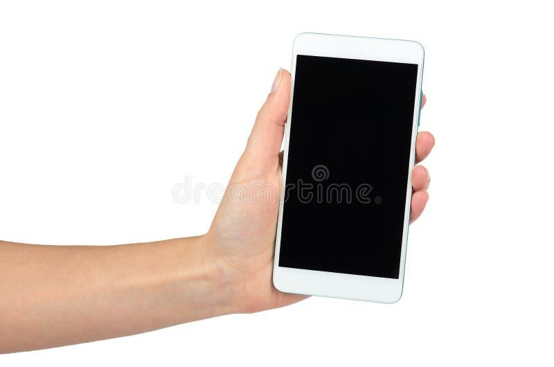 Белый мобильный телефон с темным экраном в руке, изолированной на белой предпосылке Разрекламируйте шаблон, скопируйте космос стоковые фото