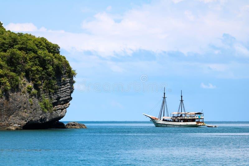 Белый парусник в океане с взглядами острова и голубого стоковые фотографии rf