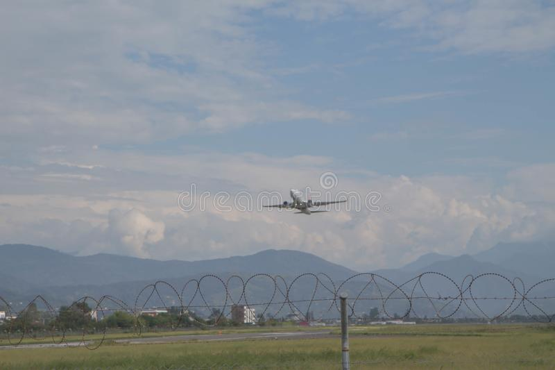 Белый пассажирский самолет летает вверх от авиапорта стоковое изображение rf