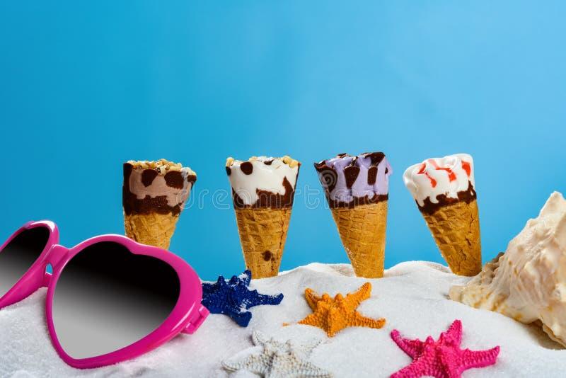 Белый песок с различной концепцией конусов и морских звёзд и солнечных очков мороженого летнего отпуска стоковая фотография