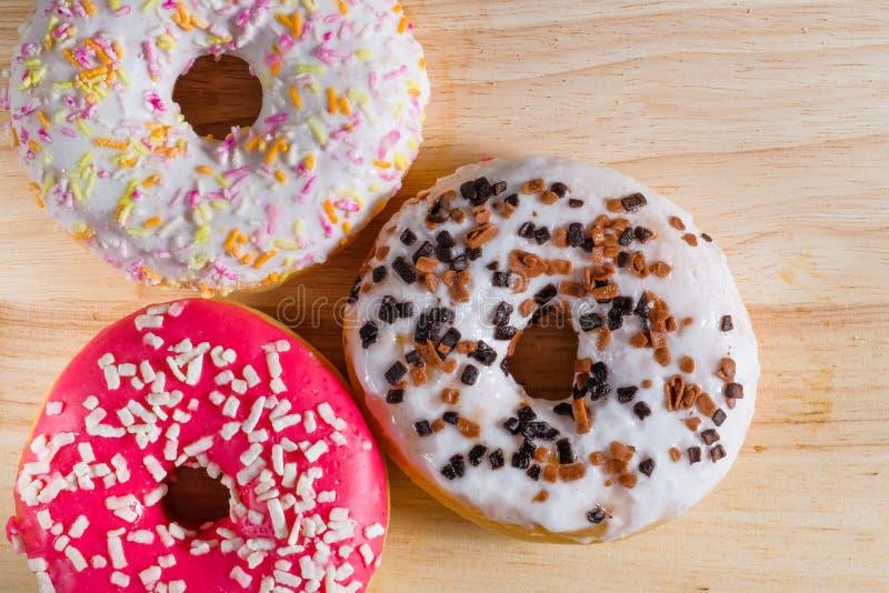 Белый, пинк и коричневый застекленный donuts на деревянной предпосылке стоковые фотографии rf