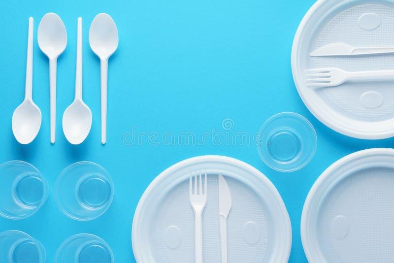 Белый пластиковый устранимый tableware на голубой предпосылке стоковые фото