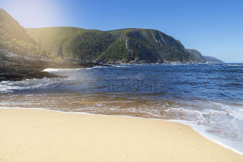 Белый пляж с взглядом, который нужно поплавать вдоль побережья в национальном парке Tsitsikmma стоковая фотография