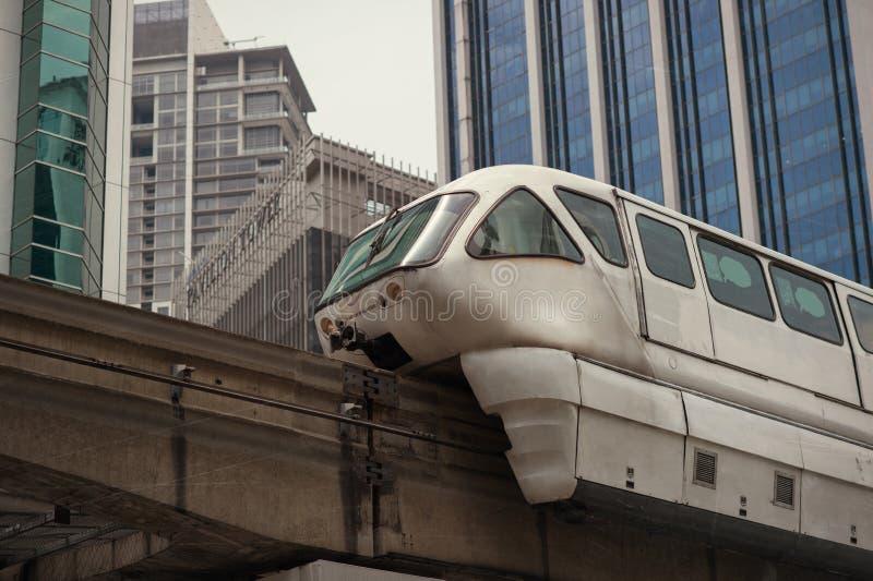 Белый поезд монорельса против голубого неба и современный небоскреб в Куалае-Лумпур стоковые фотографии rf