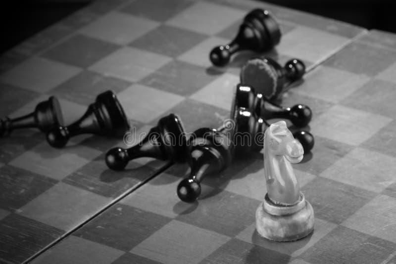 Белый рыцарь шахмат подметенный через армию враждебных пешек на старой поцарапанной доске Нападение спешкы Черная армия потерпеть стоковое изображение