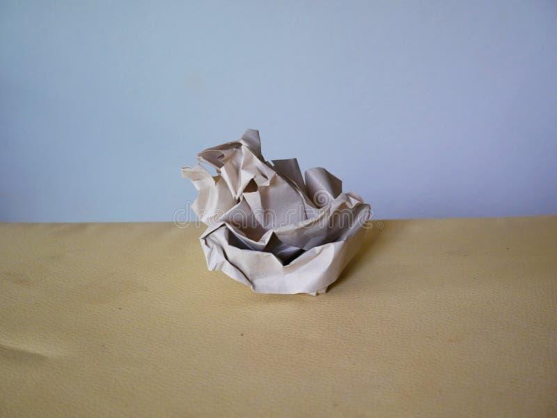Белый скомканный бумажный шарик на коричневом бумажном поле стоковые изображения
