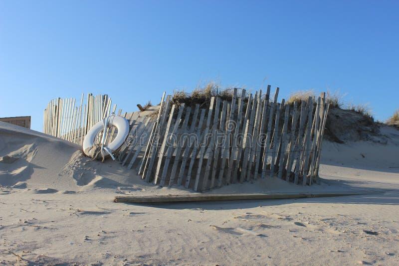 Белый спасательный жилет на песочном прибрежном пляже океана стоковые фотографии rf